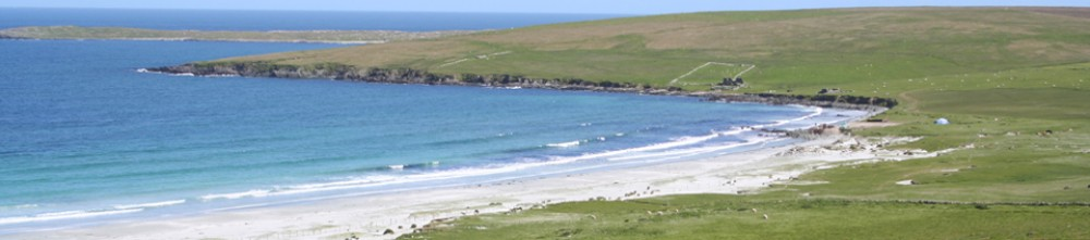 Panoramic photo of white sandy bay and calm blue sea in greeen treeless countryside