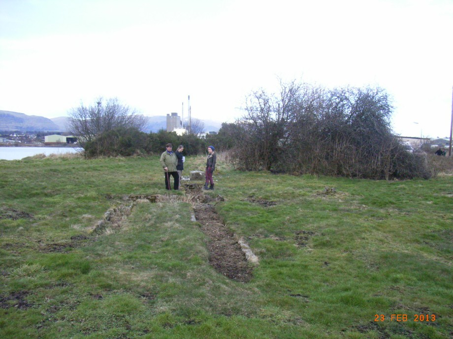 Three people standing around a narrow, concrete-edged trench in a grassy area