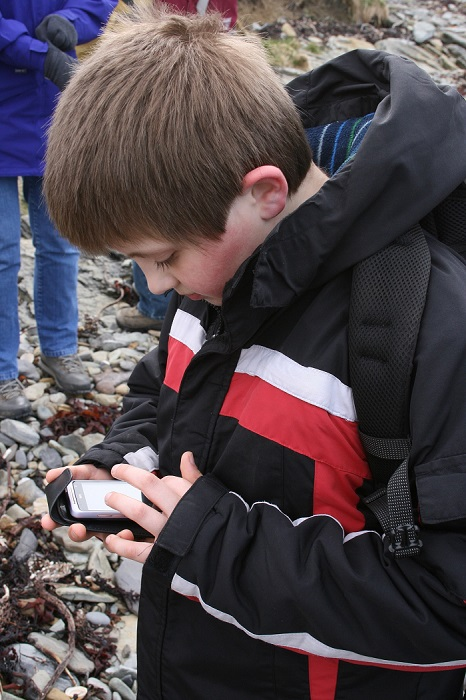 A boy using a smartphone to record an eroding archaeological site