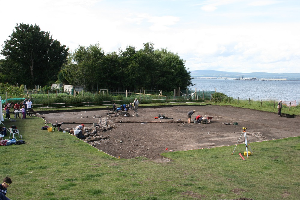 A large archaeological trench with stone walls and people in groups digging