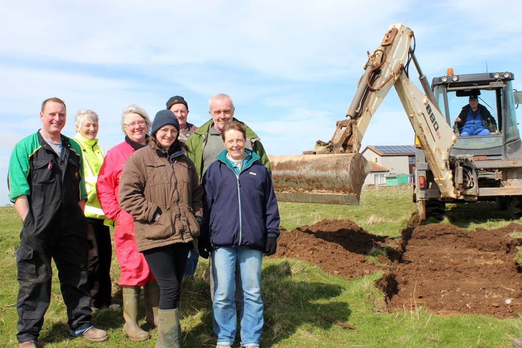 The first cut. Members of the Sanday Development Trust and the Community Council oversee the evaluation of the proposed site of the re-located Meur burnt mound.
