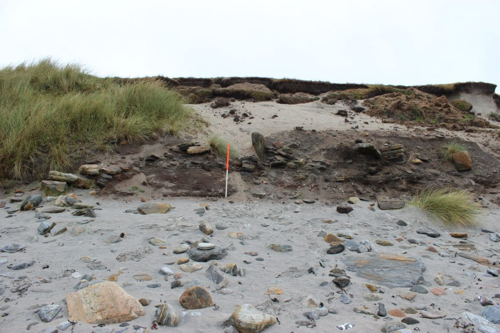 An Iron Age wheel house eroding at Baile Sear, North Uist. You are looking at the circular outside wall on the left with the stone piers and midden deposits inside.