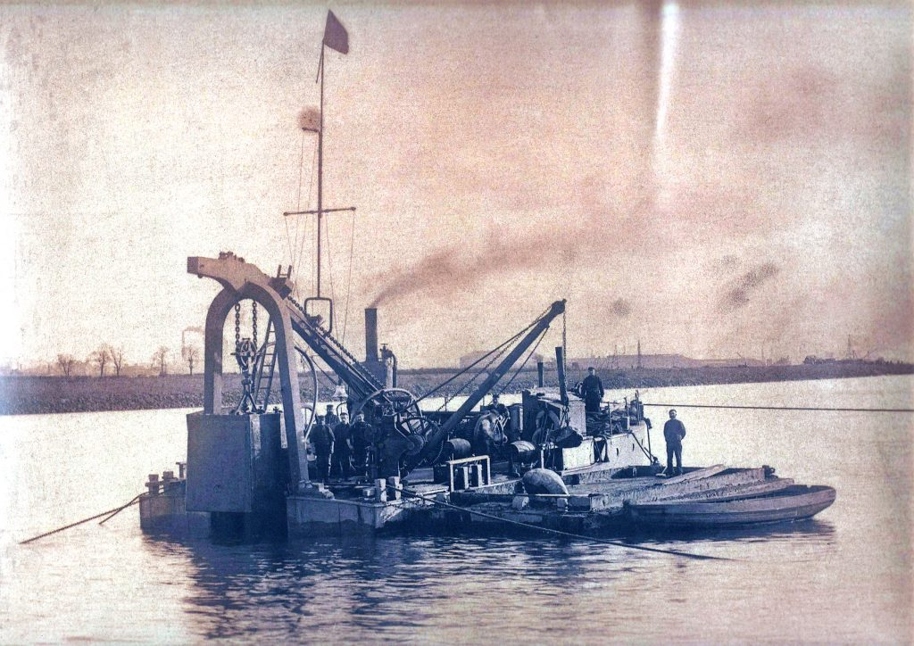 Vintage photograph of the diving bell barge with men aboard; and a mud punt a dinghy next to it.
