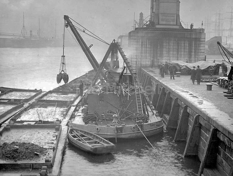 A floating crane dumps mud onto a line of floating rectangular barges, known as mud punts.