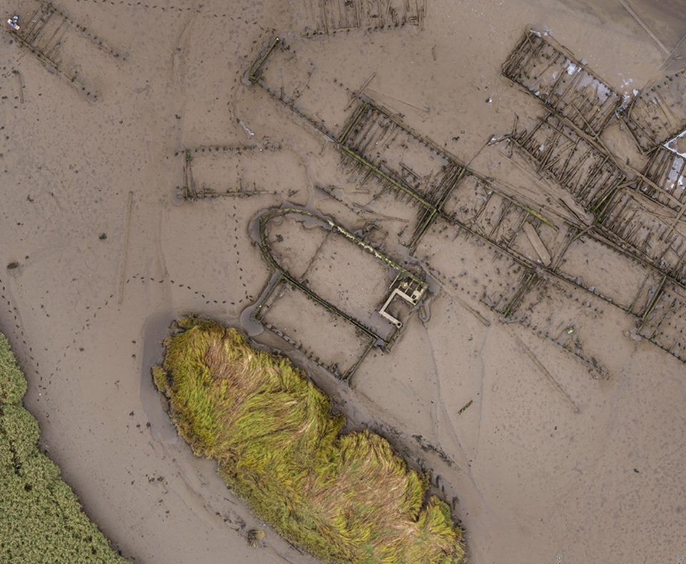 A distinctively-shaped boat at the Newshot ship graveyard, surrounded by rectangular mud punts