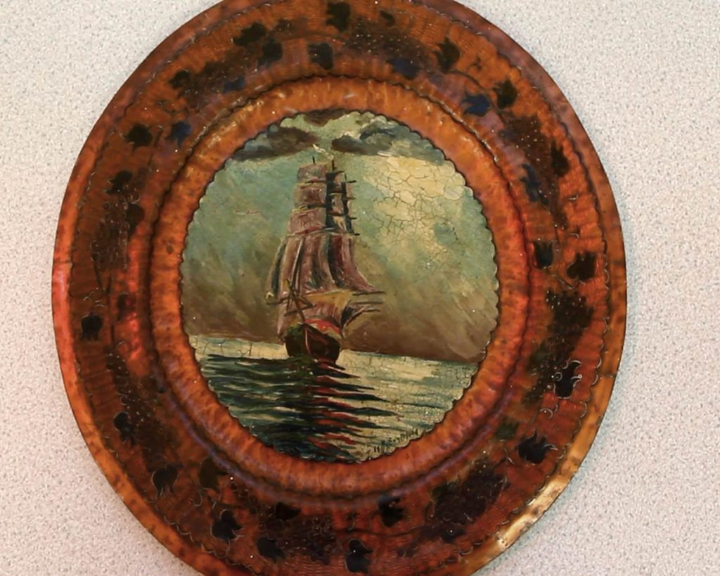 A copper plate engraved around the edges and painted with a scene of a large ship at sea