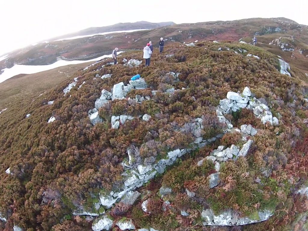 A hilltop at Bagh Moraig, with people carrying out an archaeological survey, and stone walling of a cellular structure visible.