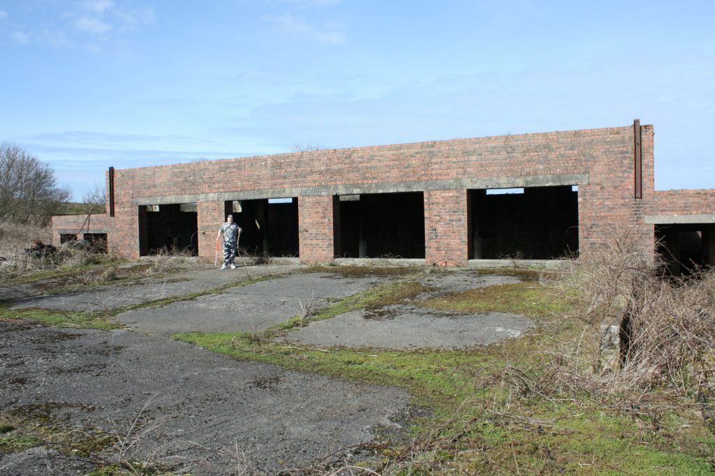 A large brick building with four large openings in the front wall, with a large area of concrete in front of it.