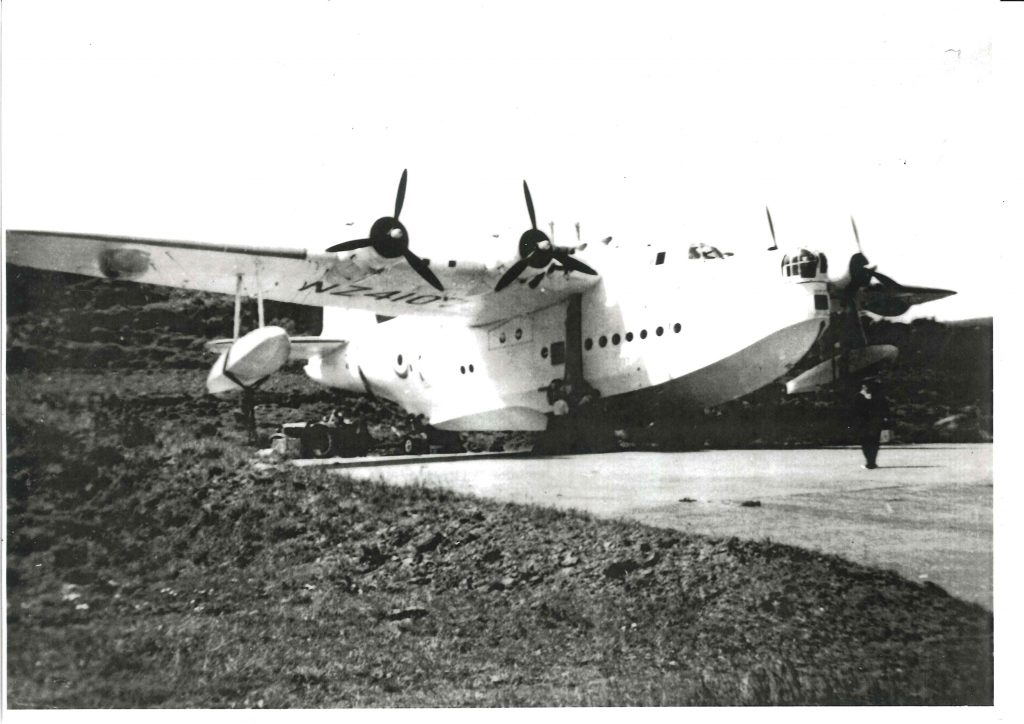 A black and white image of a large flying boat sitting on a flat concrete area terraced into a grassy slope
