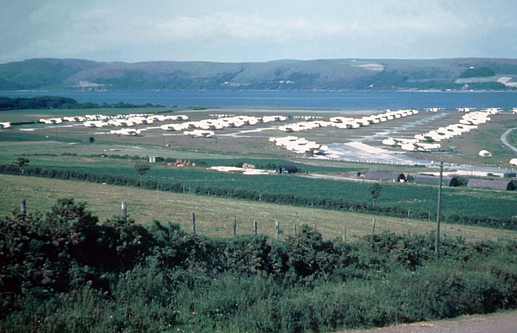 A lot of aircraft sitting parked on concrete hardstanding with a loch in the background