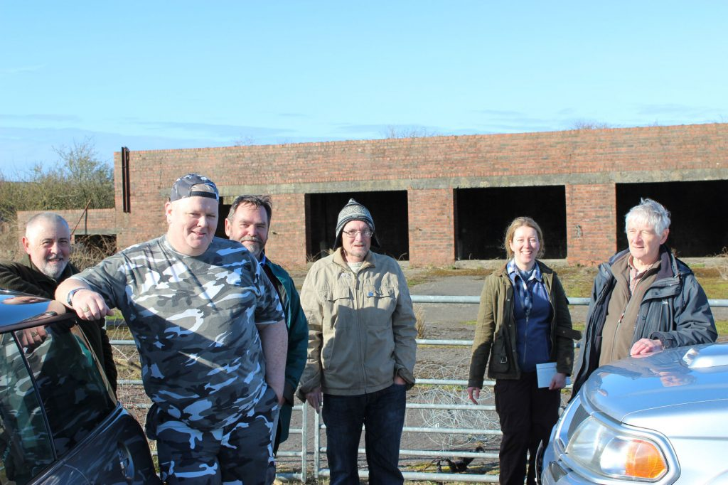 A group of people in outdoor clothing standing in front of a brick building and concrete yard