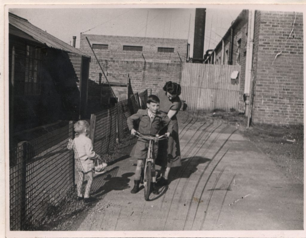 A black and white photo of a small boy sitting on a bicycle, with a woman behind him, and a toddler to one side, surrounded by brick buildings with a large chimney behind