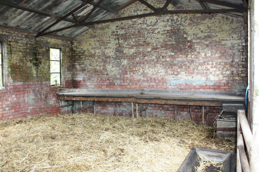 The interior of a brick building, with straw on the floor and a metal-topped bench against the back wall.