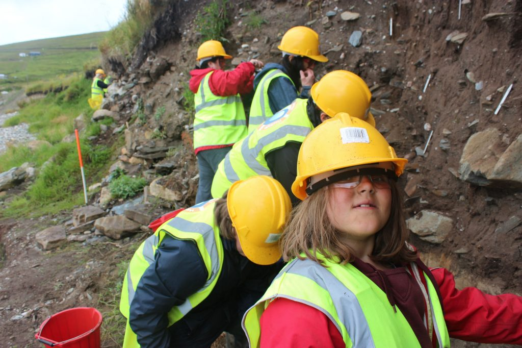 A line of people in hard hats and hi-vis jackets standing in front of an eroded coast edge