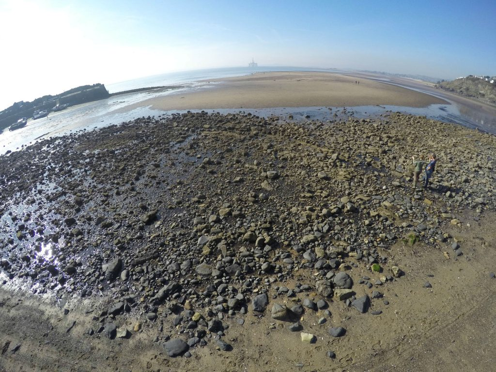 An aerial fisheye view of a sandy beach with the tide out and a large spread of stone in the foreground. A straight line of flat stones runs diagonally across the spread