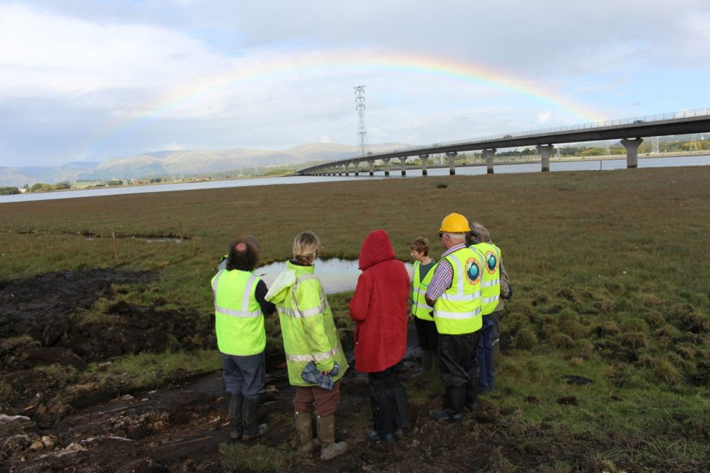 A group of people in hi-vis clothing standing on grass looking across an expanse of intertidal saltmarsh towards a distant river channel, with a rainbow on the opposite bank