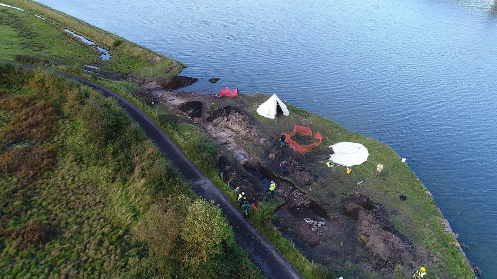 An aerial view of an archaeological trench on a grassy riverbank at high tide with water up to a stone sea wall