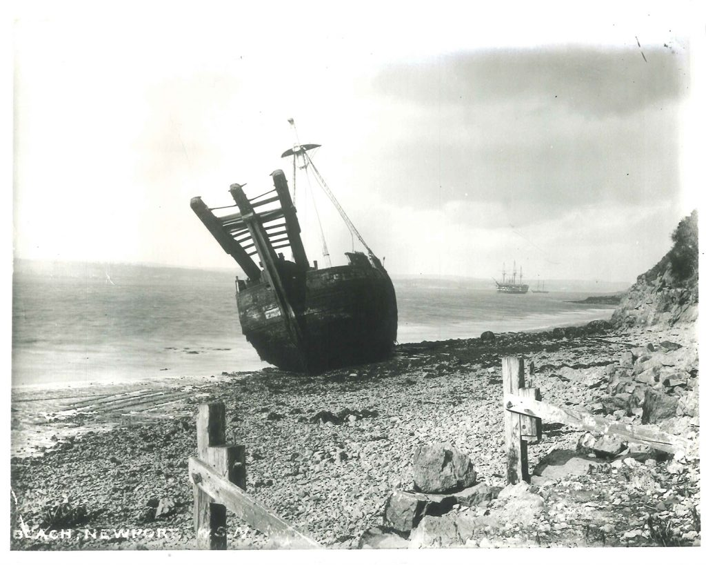 A wooden ship with three prongs on the bow sitting on the foreshore