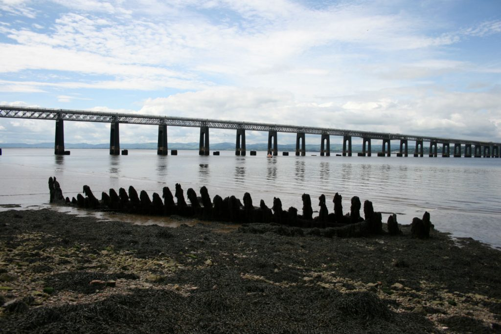 The new Tay Railway bridge, with brick pier of the old one alongside, and the ribs of a wooden boat in the foreground