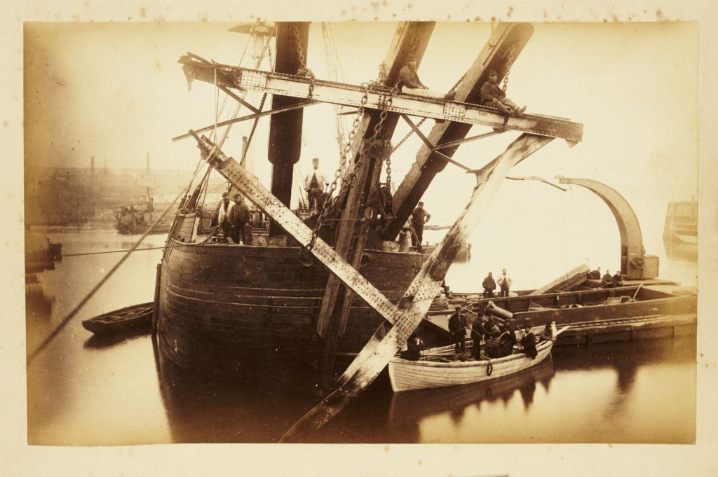 Broken metal girders hanging from chains attached to metal prongs on the bow of a ship.