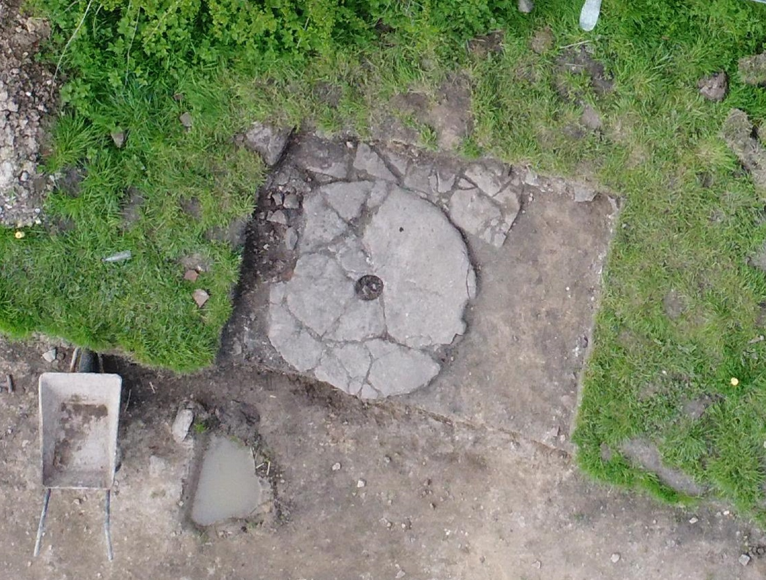 An overhead view of a circular millstone laid flat