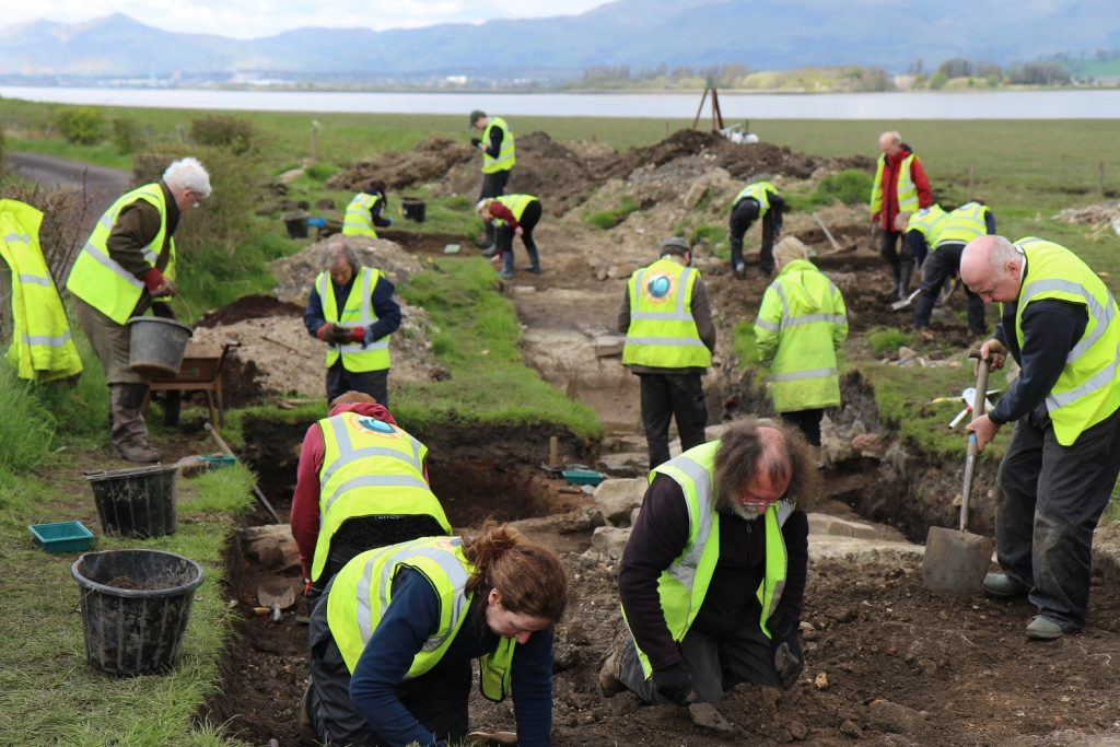 A group of people digging in an archaeological trench with a river in the background
