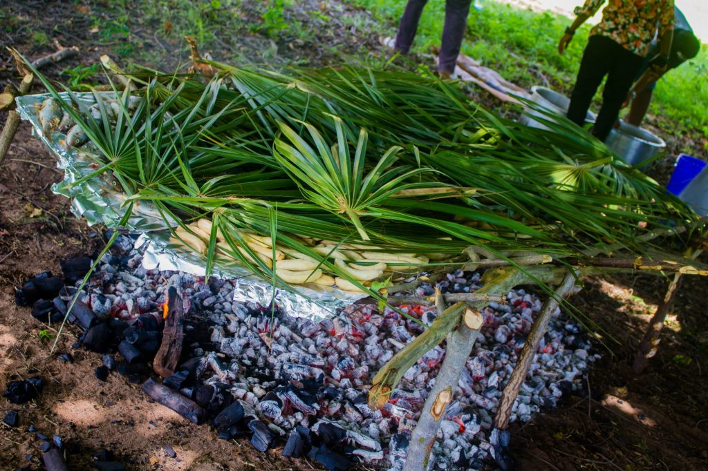 A platform covered in tinfoil over burning charcoal, piled with fish and plantain covered with palm leaves.