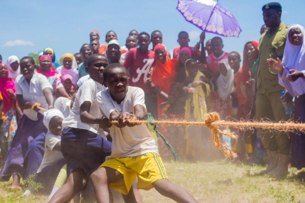 A line of children pulling on a rope while a crowd standing behind them claps and cheers.