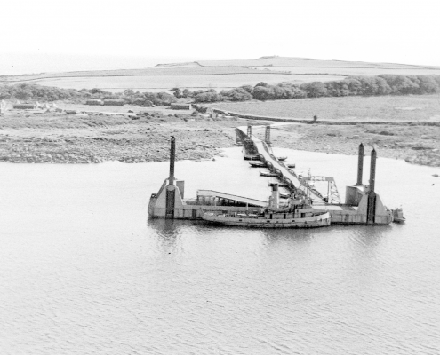 A black and white aerial photograph over the sea facing inland showing a wide pier structure with a large boat alongside, and a floating road running from it to the shore, supported by floating pontoons.