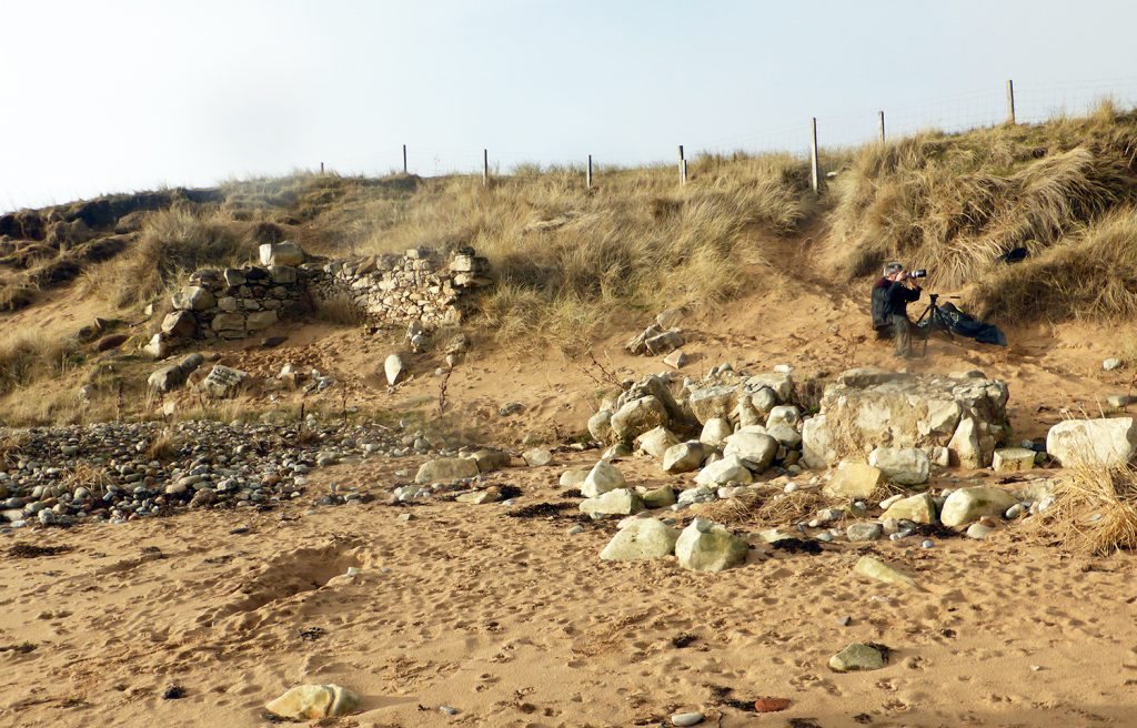 Stone building half eroded away in sand dune with collapsed stonework on beach in foreground