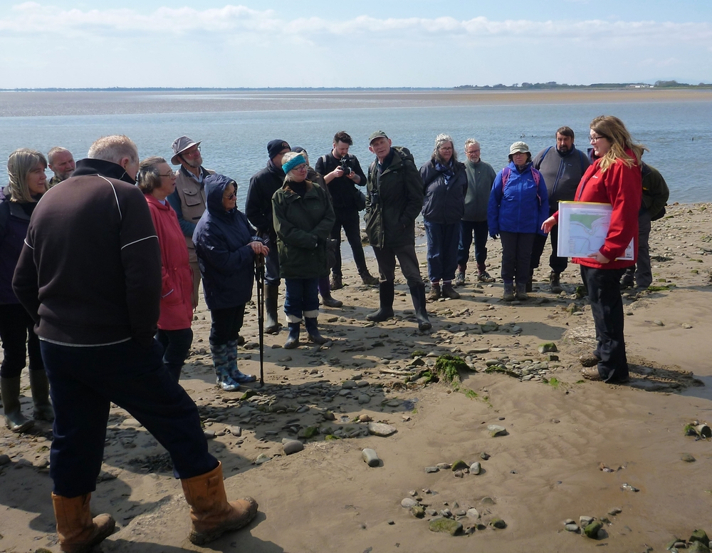 A group of people standing on the sandy bank of a tidal river listening to a woman speaking