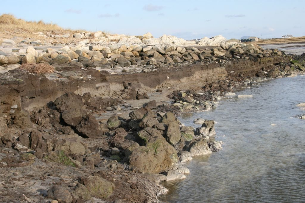 A beach with a vertical eroding face at the waters edge, and a low spread stone wall on the shore behind