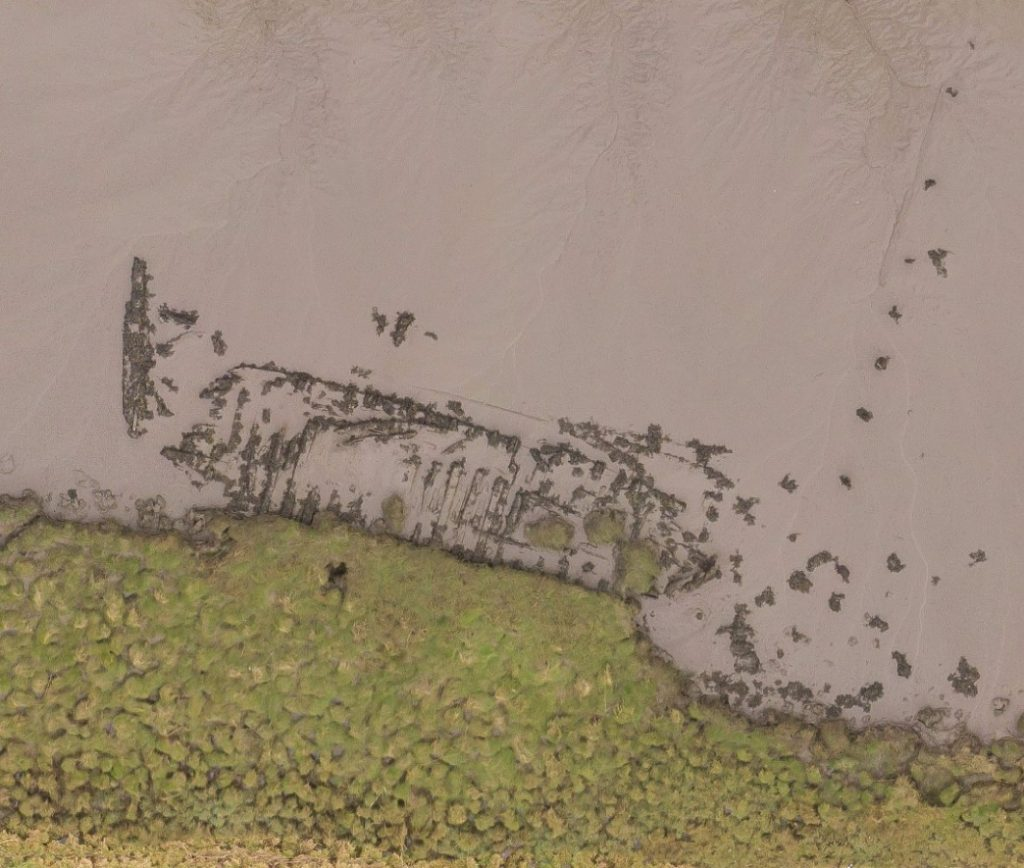 An aerial photograph of the outline of a wrecked wooden boat mostly buried in mud on a riverbank