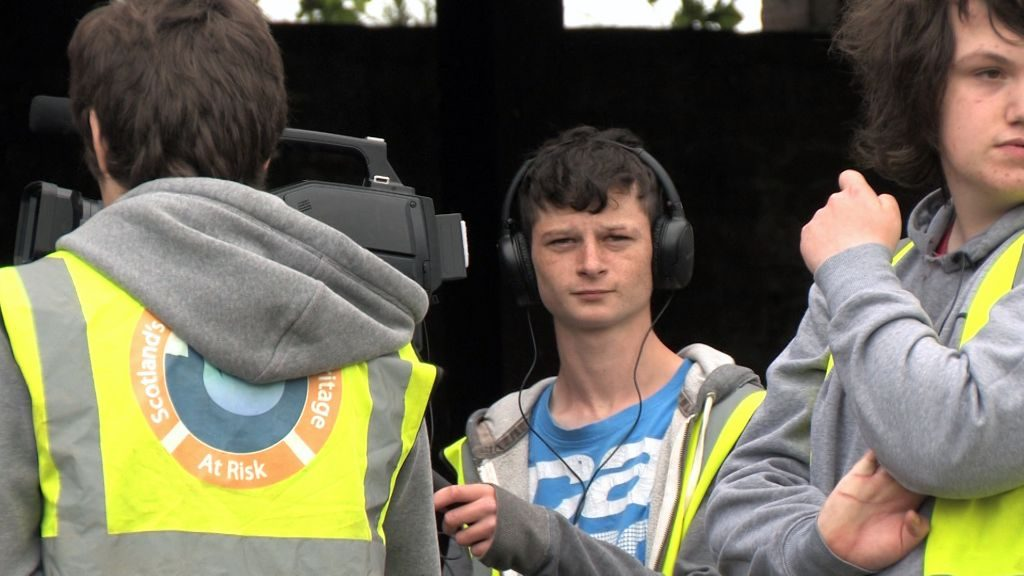 Three young people standing outside a brick building wearing hi-vis vests, earphones and operating a video camera on a tripod