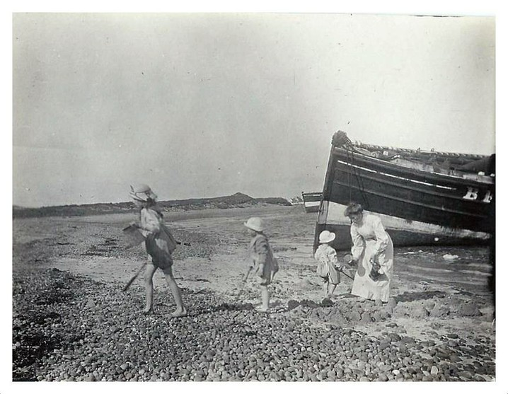 A black and white photo of three small children in summer clothes playing on a beach with large wooden boats visible on the shore behind them