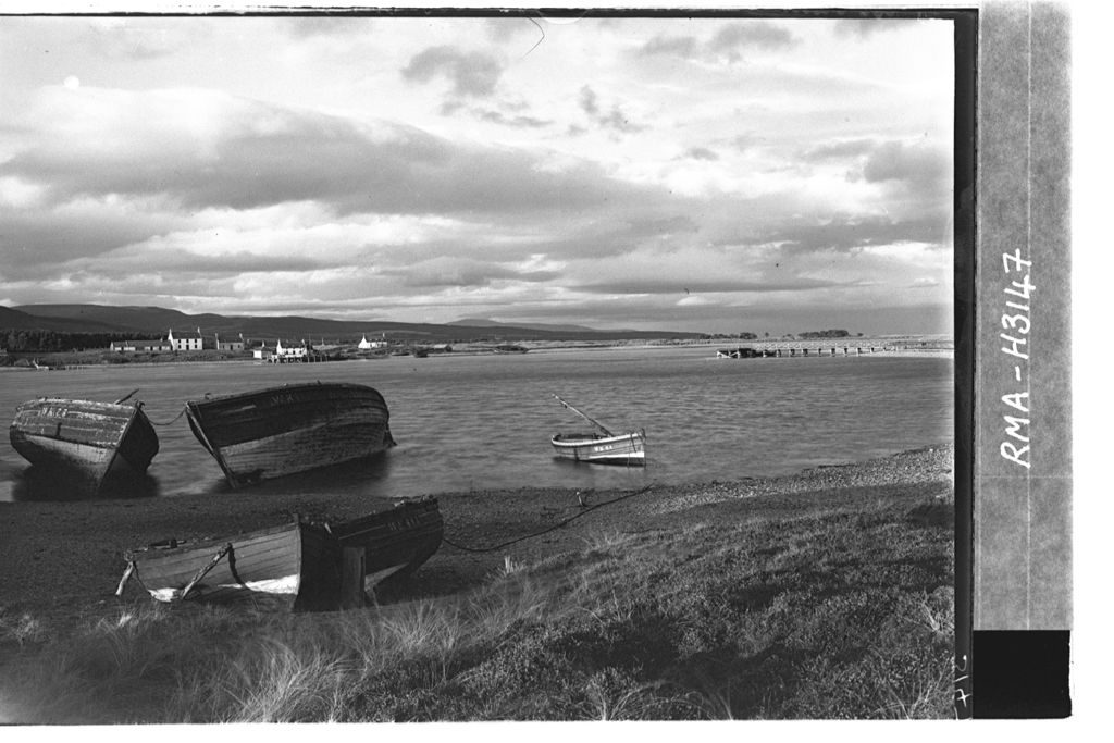 An old black and white photo of a loch with two large derelict boats pulled up on the shore and three smaller rowing boats