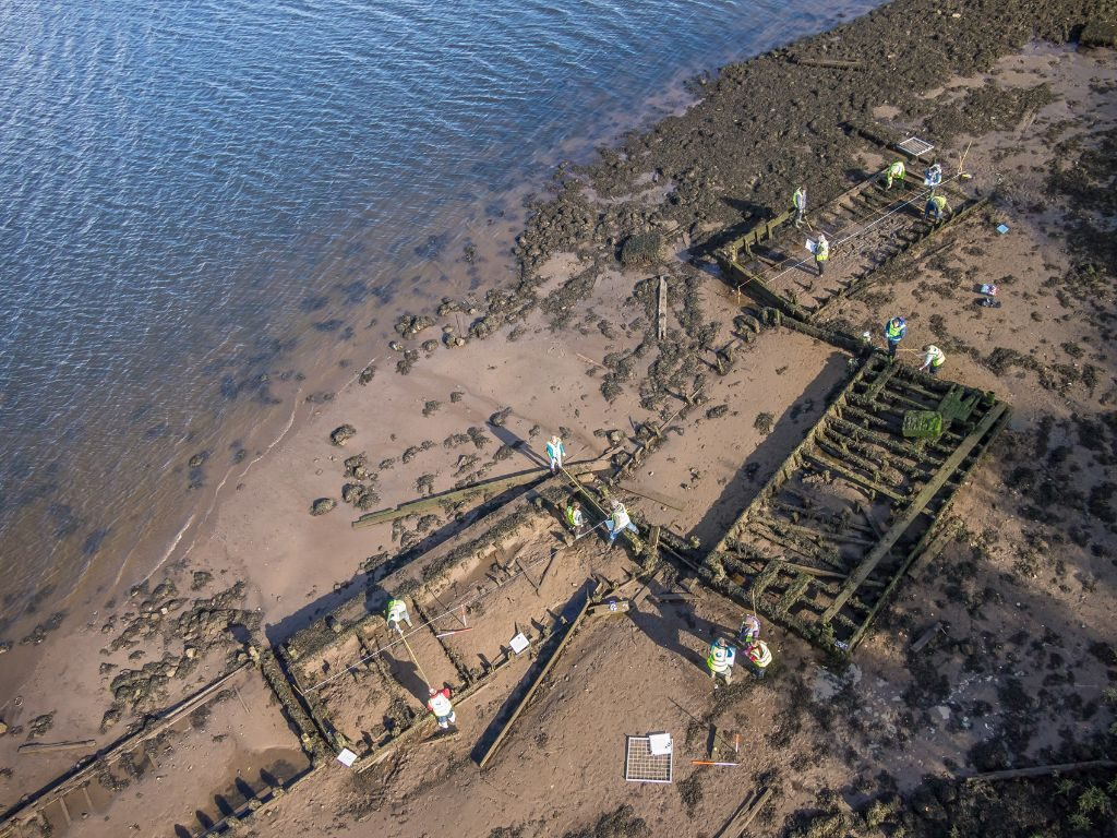 An aerial view of a group of dilapidated rectangular wooden structures half-buried in mud on the waterfront with a group of people wearing hi-vis vests dispersed around them, taking measurements and writing on clipboards