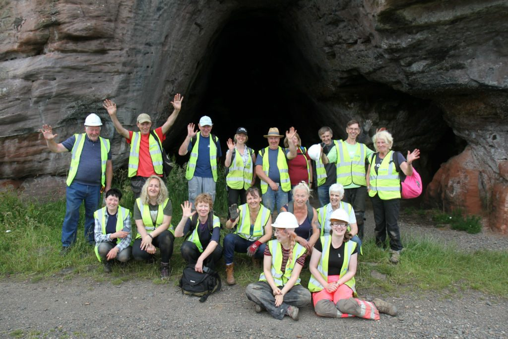 Group of people wearing high vis vests, standing and kneeling in front of a cave, smiling and waving at the camera