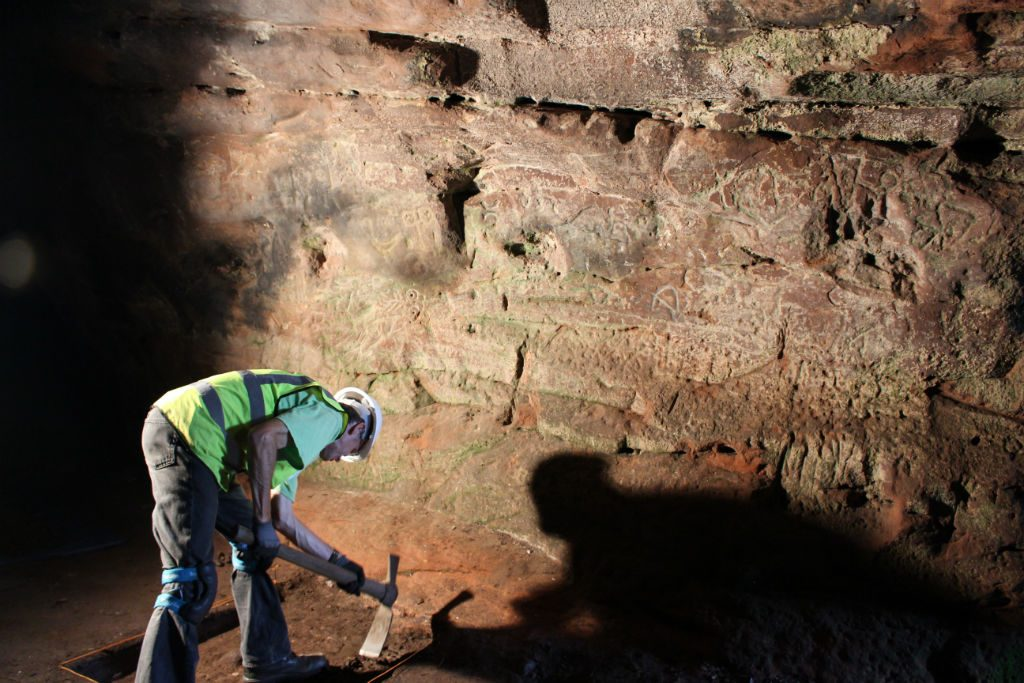Man wearing hard hat and high vis vest mattocking in front of a cave wall bearing ancient carvings