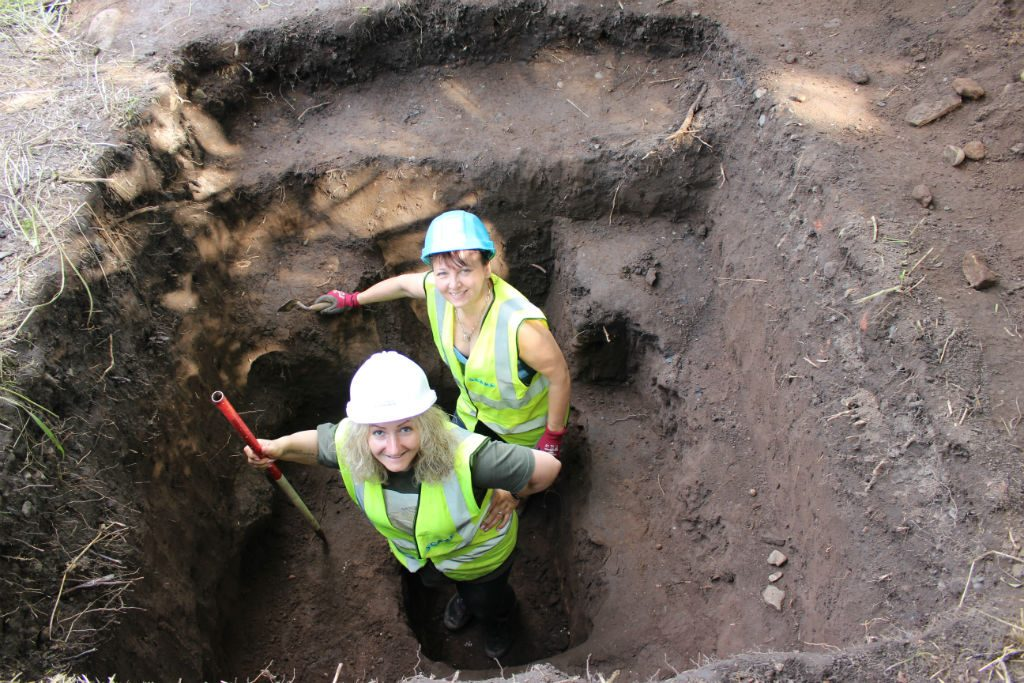 Two women wearing hard hats and high vis vests standing in an archaeological test pit smiling up at the camera