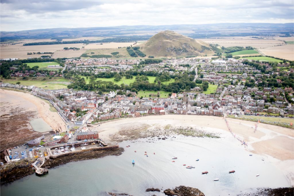 An aerial view of the town of North Berwick from the sea with North Berwick Law in the background