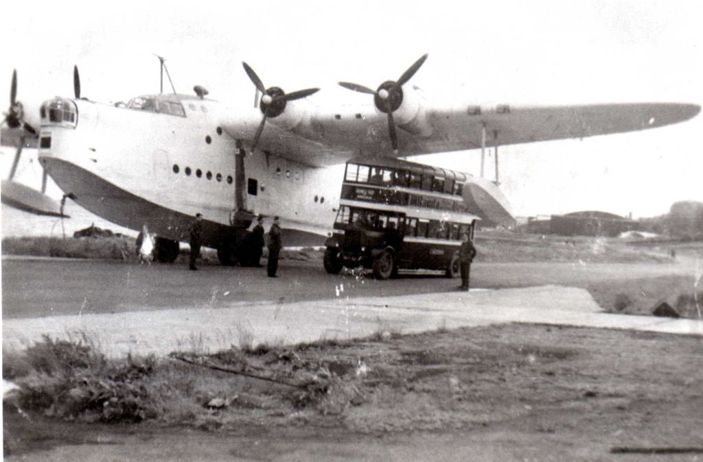 An old black and white photo of a huge flying boat being towed up a road, with an old-fashioned double-decker bus passing underneath one of its wings