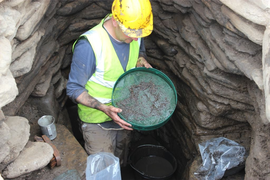 A man wearing a hard hat and hi-vis standing in an underground drystone structure holding a large seive which contains fragments of plants and other organic material