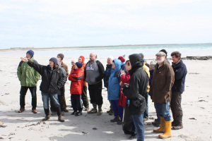 A group of people standing on a beach as one person talks and points