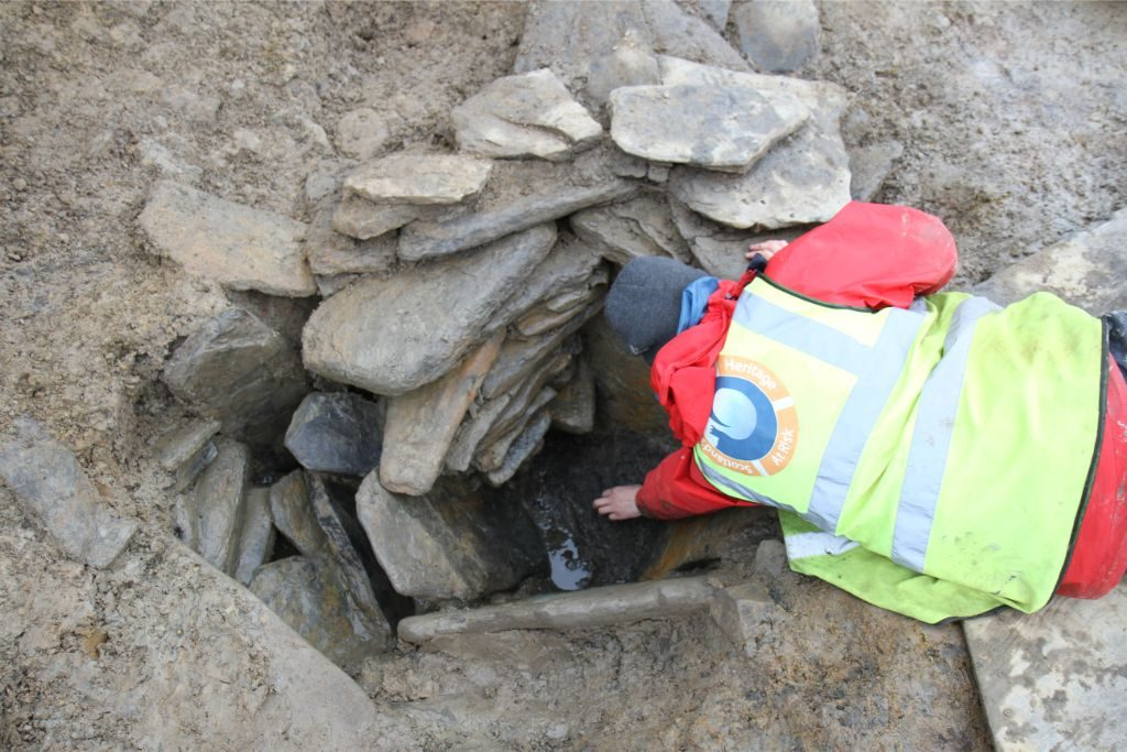 A person wearing a hi-vis vest bending down to reach into a small, stone-lined hole in the ground
