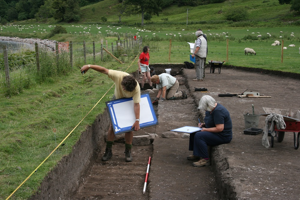An archaeological trench, with people measuring and drawing in the foreground, and people with folders and paperwork in the background