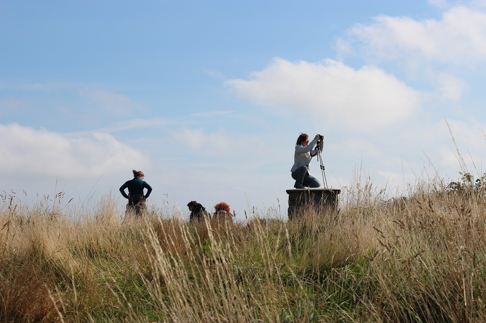 A grassy hill with a group of people on the horizon, one filming with a camera on a tripod