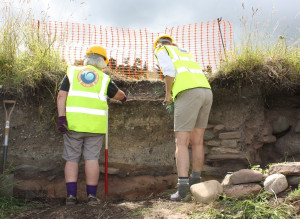 Babs and Pat carefully excavating layers of ash, shellfish and fish bone next to what could be a medieval wall