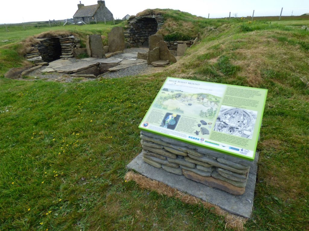 Stone structures built of large upright flagstones forming small compartments with corbelled drystone structures, capped with turf, in a grassy area with a large interpretation board in the forground
