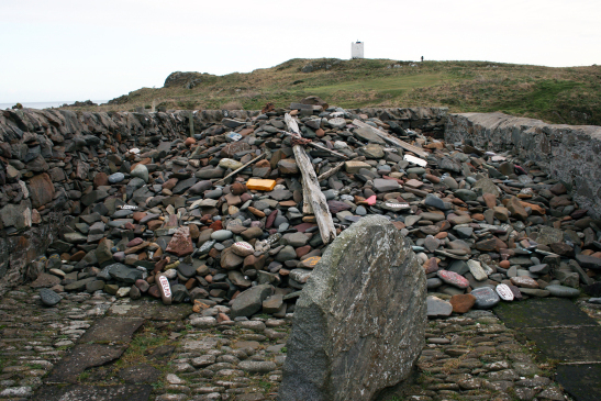 A large pile of stones inside a low enclosing stone wall